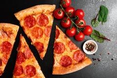 Rebanadas de la pizza de salchichones en la opinión superior del fondo negro imagen de archivo libre de regalías