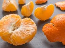 Rebanadas de las mandarinas en fondo negro Mandarín anaranjado Imagen de archivo libre de regalías