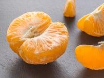 Rebanadas de las mandarinas en fondo negro Mandarín anaranjado Fotos de archivo libres de regalías