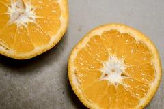 Rebanadas de las naranjas y fondo marrón Fotos de archivo