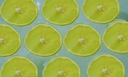 Rebanadas de limón maduro en un fondo azul claro imagen de archivo