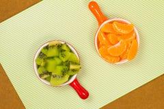 Rebanadas de mandarina en una taza roja Rebanadas de fruta de kiwi Imágenes de archivo libres de regalías