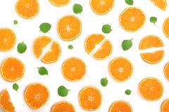 Rebanadas de naranja o de mandarina con las hojas de menta aisladas en el fondo blanco Endecha plana, visión superior Composición Imagenes de archivo