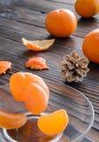 rebanadas de naranja y de una mandarina madura en el platillo de cristal Contra el fondo la tabla de madera vieja Fotos de archivo libres de regalías