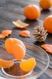 rebanadas de naranja y de una mandarina madura en el platillo de cristal Contra el fondo la tabla de madera vieja Imagen de archivo libre de regalías