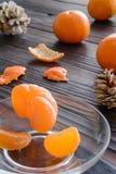 rebanadas de naranja y de una mandarina madura en el platillo de cristal Contra el fondo la tabla de madera vieja Fotografía de archivo