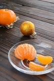 rebanadas de naranja y de una mandarina madura en el platillo de cristal Contra el fondo la tabla de madera vieja Foto de archivo