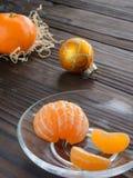 rebanadas de naranja y de una mandarina madura en el platillo de cristal Contra el fondo la tabla de madera vieja Fotografía de archivo libre de regalías