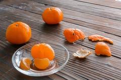 rebanadas de naranja y de una mandarina madura en el platillo de cristal Contra el fondo la tabla de madera vieja Fotos de archivo