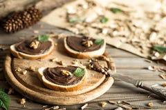 Rebanadas de pan con las nueces y el cuchillo de la crema del chocolate Imágenes de archivo libres de regalías