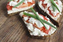 Rebanadas de pan de centeno con queso Feta, el tomate y la cebolla del padre imagen de archivo libre de regalías