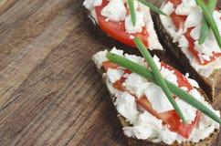 Rebanadas de pan de centeno con queso Feta, el tomate y la cebolla del padre imagen de archivo