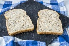 Rebanadas de pan del trigo en tabla de cortar negra un mantel azul foto de archivo libre de regalías