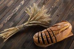 Rebanadas de pan en una tabla de cortar y los oídos del trigo en la madera Imagen de archivo