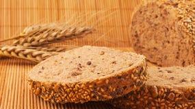 Rebanadas de pan orgánico adornadas con los cereales naturales en fondo y trigo de madera Imagen de archivo libre de regalías