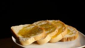 Rebanadas de pan tostado con fluir abajo de la miel en fondo negro Fotos de archivo libres de regalías