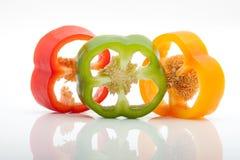 Rebanadas de pimienta roja, verde, amarilla y anaranjada aislada en el fondo blanco Foto de archivo libre de regalías