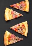 Rebanadas de pizza recientemente cocida en la superficie negra, visión superior Endecha plana, de arriba imagenes de archivo