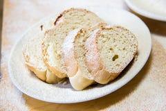 Rebanadas de Poudered de pan en una placa blanca en la tabla Imagenes de archivo