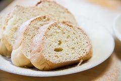 Rebanadas de Poudered de pan en una placa blanca en la tabla Imágenes de archivo libres de regalías