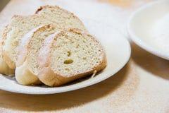 Rebanadas de Poudered de pan en una placa blanca en la tabla Fotos de archivo
