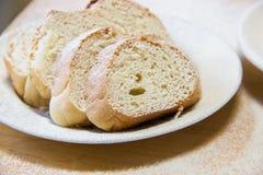 Rebanadas de Poudered de pan en una placa blanca en la tabla Imagen de archivo