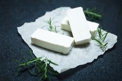 Rebanadas de queso feta con romero en el papel de pergamino foto de archivo libre de regalías