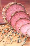 Rebanadas de salami con los granos de la pimienta Fotos de archivo libres de regalías