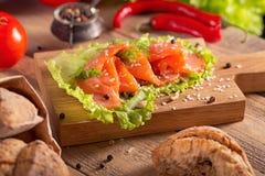 Rebanadas de salmón ahumado con eneldo, pimienta de chile, los tomates y el Br fotografía de archivo libre de regalías