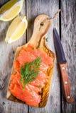 Rebanadas de salmón ahumado en una tajadera de madera con eneldo Fotos de archivo libres de regalías