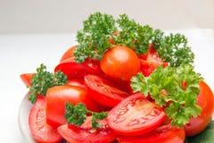 Rebanadas de tomate maduro rojo y de hierbas frescas en una placa en la cocina Aún lifes auténticos naturales Imagen de archivo libre de regalías