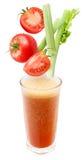Rebanadas de tomate y de apio que caen en un vidrio o Fotografía de archivo