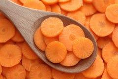 Rebanadas de zanahoria fresca en una cuchara de madera Imagen de archivo libre de regalías