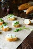 Rebanadas del Baguette con queso verde y arugula fresco Imágenes de archivo libres de regalías