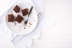 Rebanadas del brownie en una placa blanca en la servilleta blanca en el fondo de madera blanco imagen de archivo