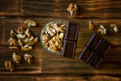Rebanadas del chocolate y nueces peladas en una superficie de madera marrón Aún vida rústica imagen de archivo libre de regalías