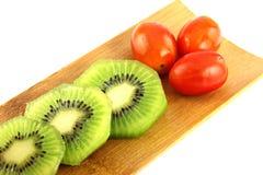 Rebanadas del kiwi en pedazos y el tomate tres. Fotos de archivo