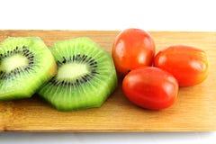 Rebanadas del kiwi en pedazos y el tomate tres. Fotografía de archivo libre de regalías