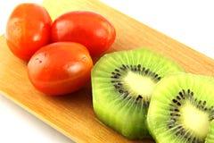 Rebanadas del kiwi en pedazos y el tomate tres. Imagen de archivo