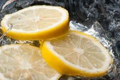 Rebanadas del limón del chapoteo del agua Imágenes de archivo libres de regalías