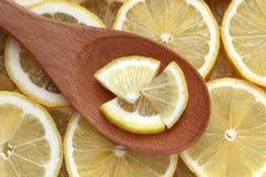 Rebanadas del limón en una cuchara de madera Foto de archivo