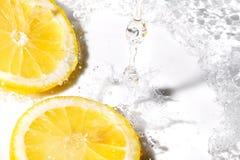 Rebanadas del limón y chapoteo del agua foto de archivo
