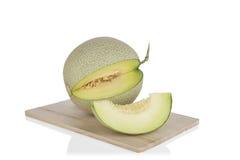 Rebanadas del melón del cantalupo en tabla de cortar de madera en el fondo blanco Con la trayectoria de recortes Imágenes de archivo libres de regalías