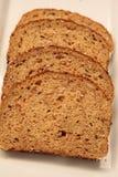 Rebanadas del pan del multigrain de Brown en una placa blanca Imagen de archivo libre de regalías
