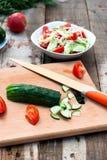 Rebanadas del pepino y del tomate en una tarjeta de corte Foto de archivo libre de regalías
