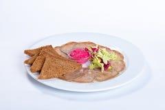 Rebanadas del plato de la lengua con la ensalada y el pan Fotos de archivo