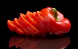 Rebanadas del primer de paprikas rojos aislados en negro Fotos de archivo libres de regalías