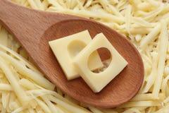Rebanadas del queso con los agujeros en una cuchara de madera Imágenes de archivo libres de regalías