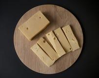 Rebanadas del queso en la opini?n superior de la tabla de cortar de madera redonda fotografía de archivo libre de regalías