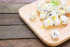 Rebanadas del queso Feta en tabla de cortar foto de archivo